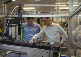 Co-owners inspect equipment in a battery manufacturing company